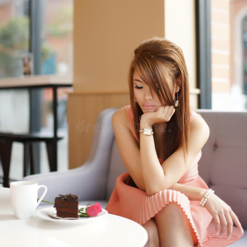 Mulher bonita nova que senta-se no café e que olha a cor-de-rosa.   fotografia de stock