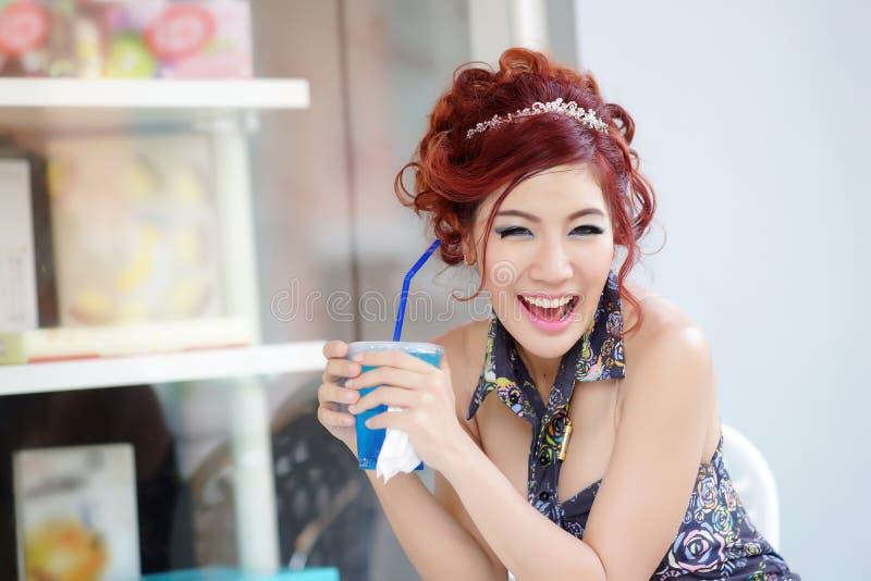 Mulher bonita nova que senta-se no café exterior que guardara o refresco fotografia de stock
