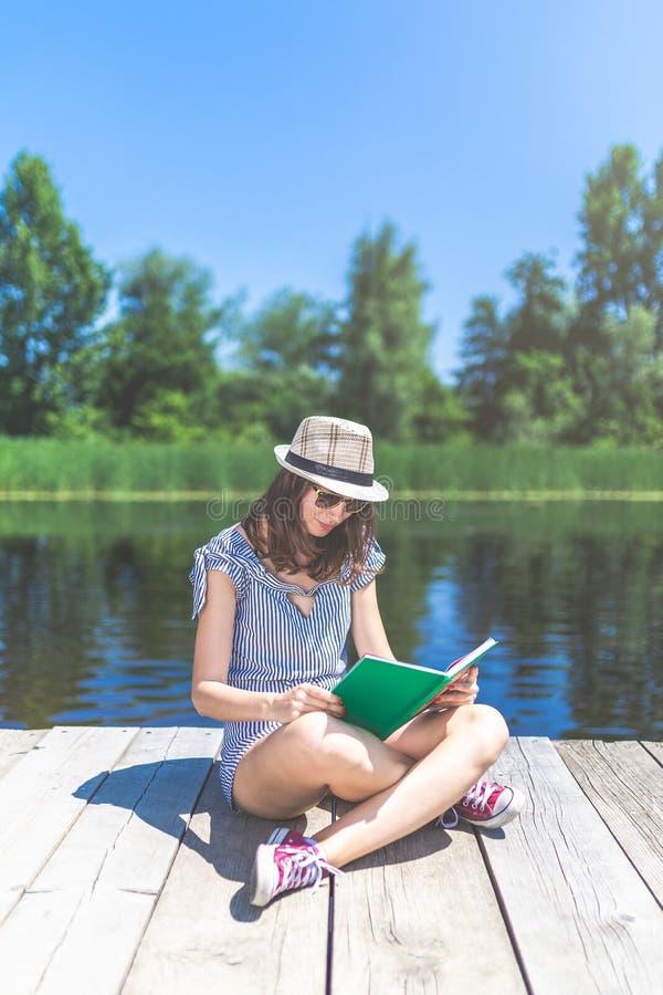Mulher bonita nova que senta-se no cais e no livro de leitura Natureza bonita no fundo foto de stock