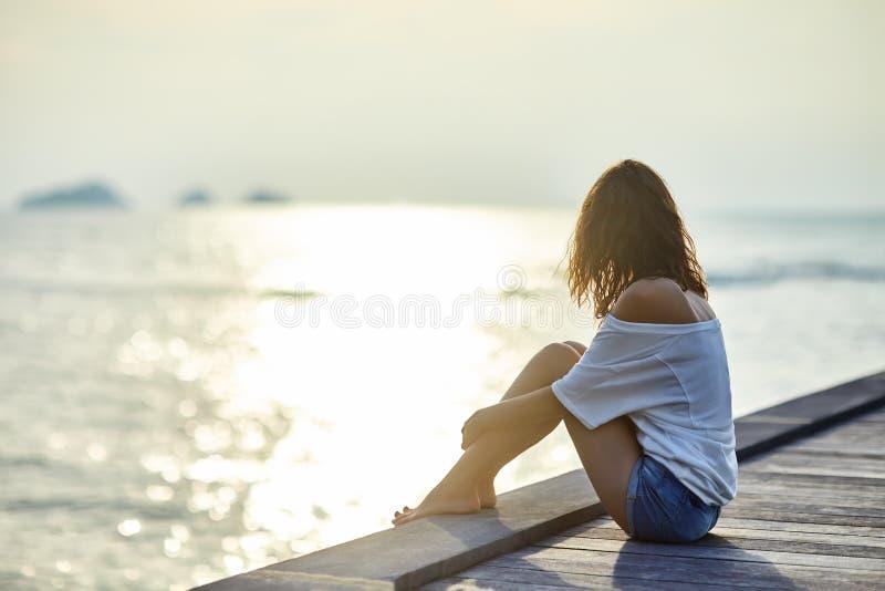Mulher bonita nova que senta-se no cais que aprecia o por do sol imagens de stock