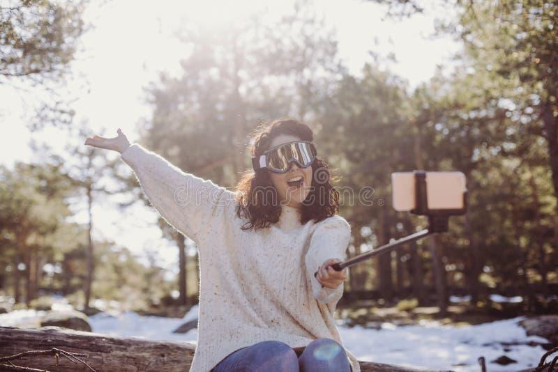 Mulher bonita nova que senta-se nos troncos de madeira e que toma uma imagem com telefone celular Óculos de proteção vestindo do  fotografia de stock