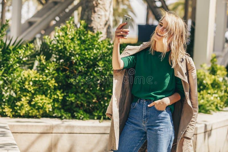 Mulher bonita nova que sorri brilhantemente ao guardar o telefone esperto que dá uma volta na cidade no dia ensolarado imagens de stock