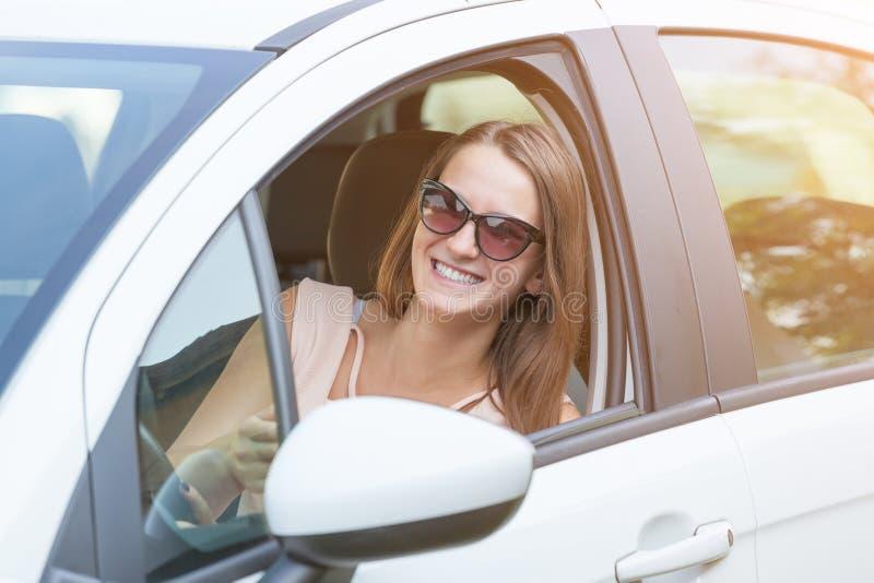Mulher bonita nova que sorri do carro fotografia de stock