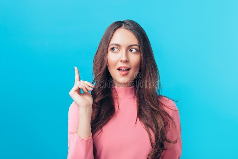 Mulher bonita nova que tem a boa ideia com seu dedo que aponta acima do isolado no fundo azul foto de stock