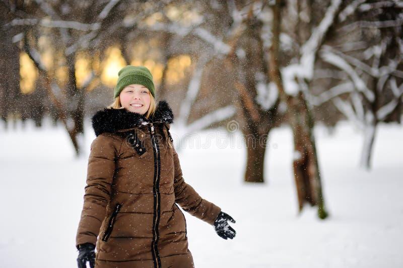 Mulher bonita nova que tem o divertimento no parque do inverno imagem de stock