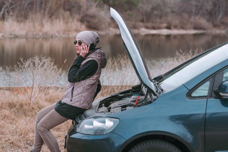 Mulher bonita nova que tem o problema com carro e que chama para a ajuda imagem de stock royalty free