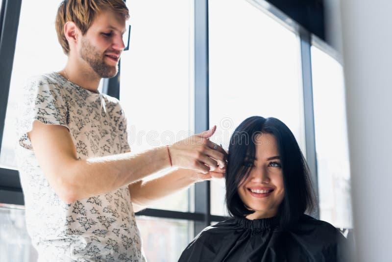 Mulher bonita nova que tem seu cabelo cortado no ` s do cabeleireiro Cabeleireiro masculino novo que sorri e que faz o penteado a fotos de stock