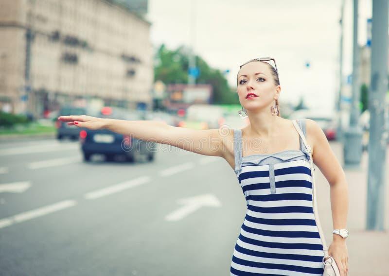 Mulher bonita nova que tenta saudar um táxi na cidade imagem de stock royalty free