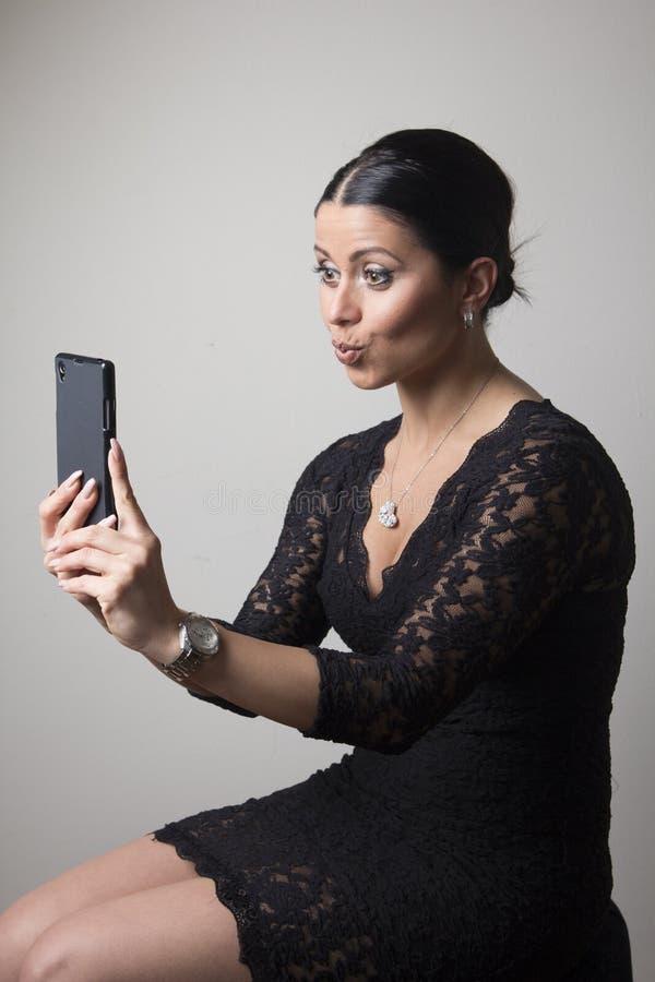 Mulher bonita nova que toma um selfie em sua câmera do telefone imagem de stock royalty free
