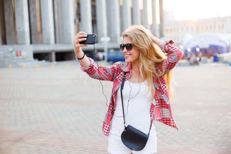 Mulher bonita nova que toma um selfie no quadrado na cidade imagens de stock