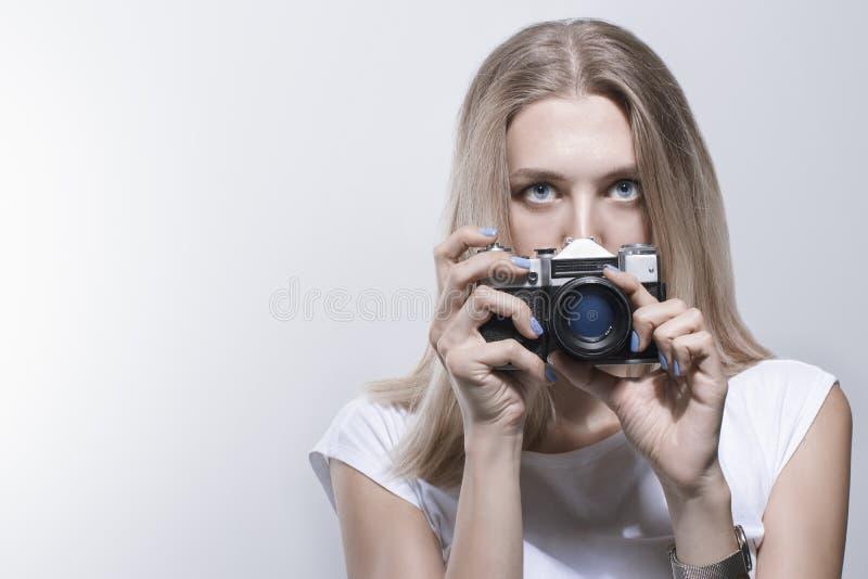 Mulher bonita nova que toma uma foto com uma câmera retro imagem de stock