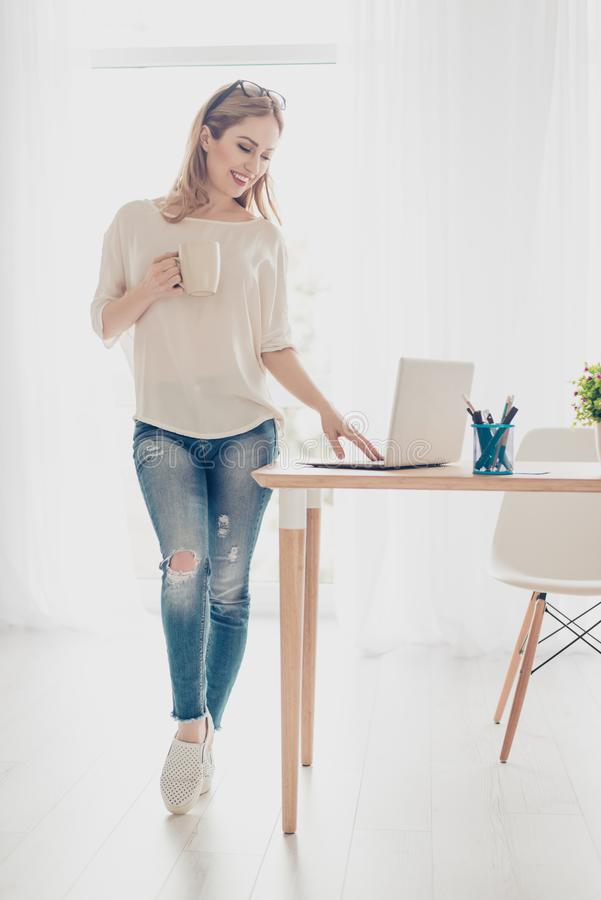 Mulher bonita nova que trabalha com o portátil que está a letra de datilografia do email da tabela próxima no netwbook Estar na a foto de stock