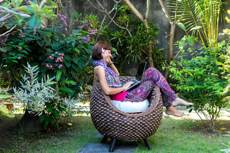 Mulher bonita nova que trabalha com o portátil no parque tropical exterior, no sorriso e no sentimento de relaxamento feliz na ma imagem de stock royalty free
