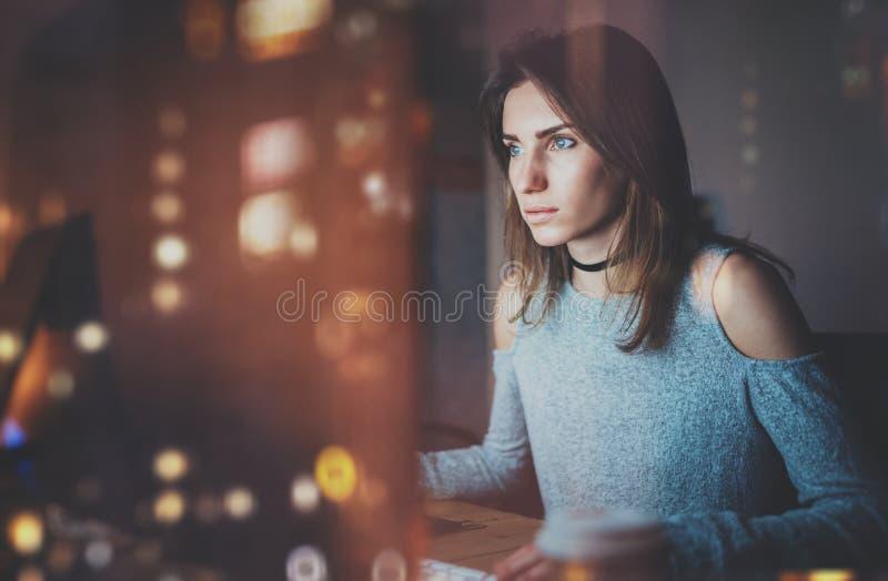Mulher bonita nova que trabalha no escritório moderno do sótão na noite Menina que usa o computador de secretária contemporâneo,  imagens de stock