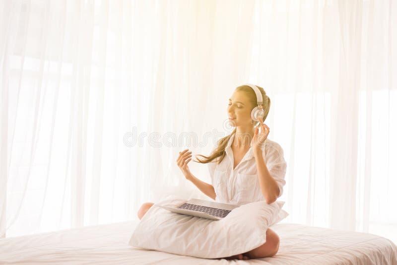 Mulher bonita nova que usa o fones de ouvido e escutando a música e a dança no quarto, no tempo, em feliz de relaxamento e sorris fotos de stock royalty free