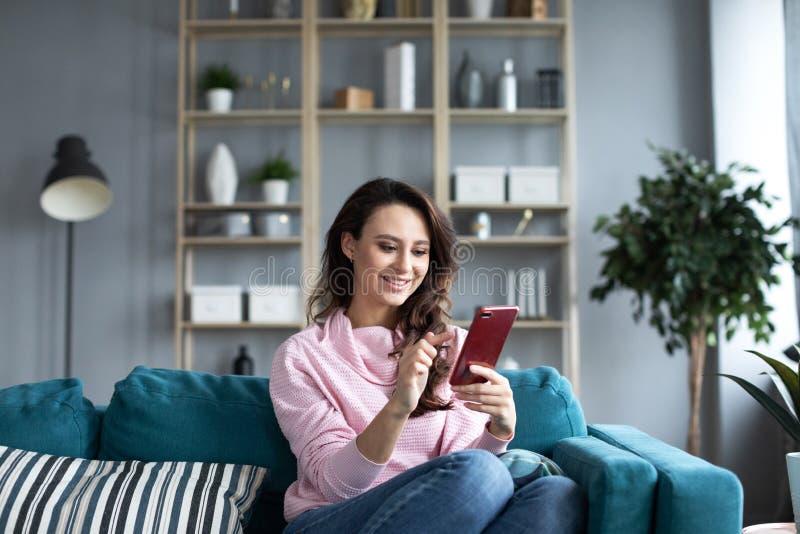 Mulher bonita nova que usa o smartphone em casa foto de stock royalty free