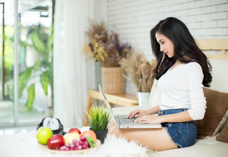 Mulher bonita nova que usa um laptop imagem de stock