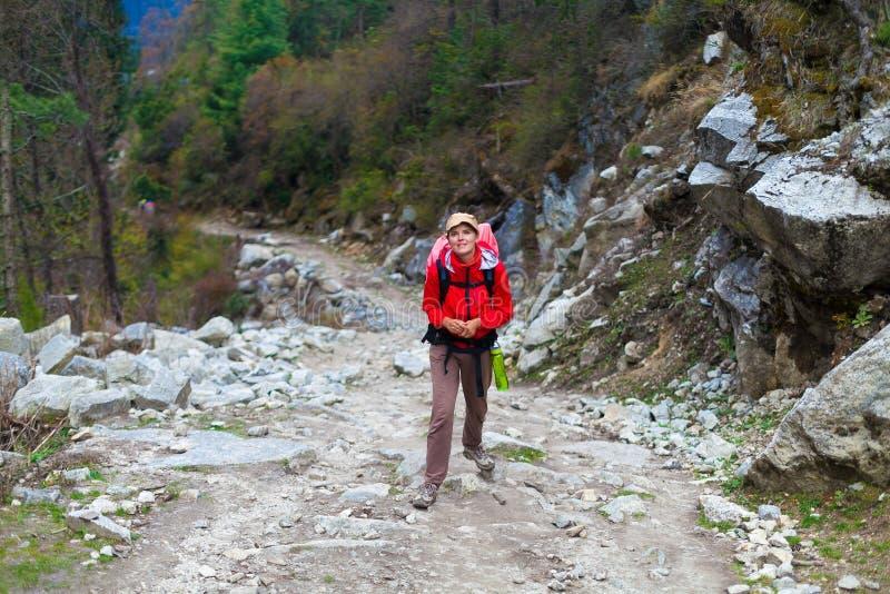 Mulher bonita nova que veste montanhas vermelhas da fuga da trouxa do revestimento Fundo Trekking da opinião da paisagem do traje fotografia de stock
