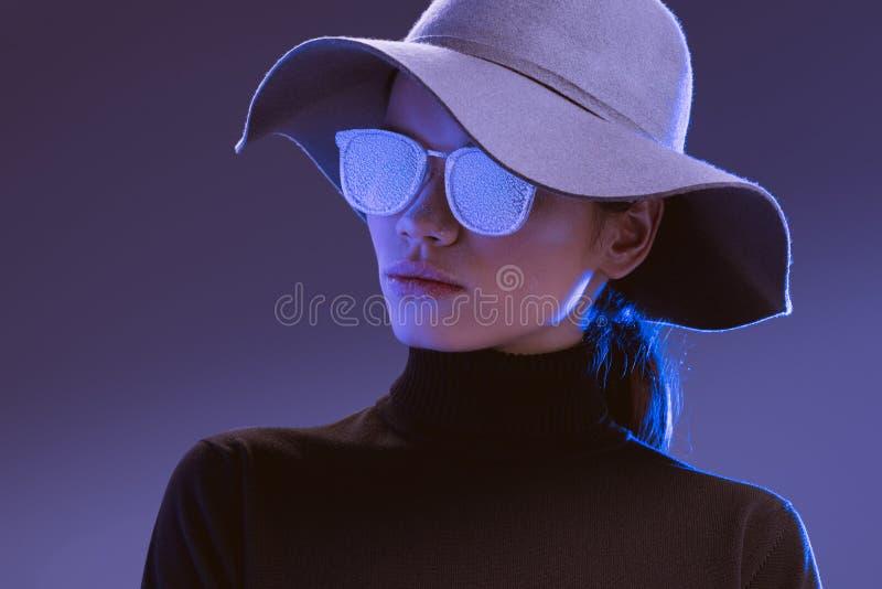 Mulher bonita nova que veste o chapéu largo-brimmed e os óculos de sol cobertos imagens de stock