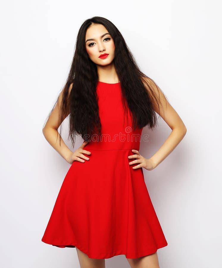 Mulher bonita nova que veste o vestido vermelho que levanta sobre o fundo branco imagens de stock royalty free