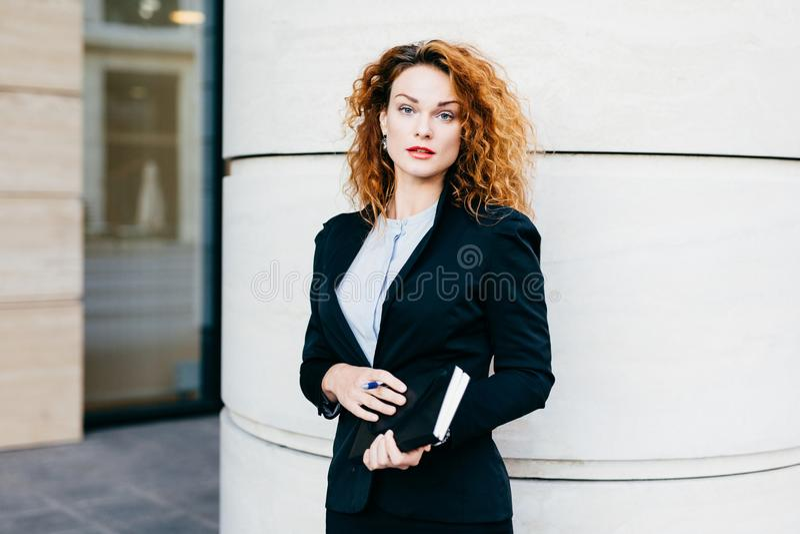 Mulher bonita nova que veste a roupa formal, vestida formalmente, guardando o livro de bolso com pena, tendo o penteado espesso,  imagens de stock