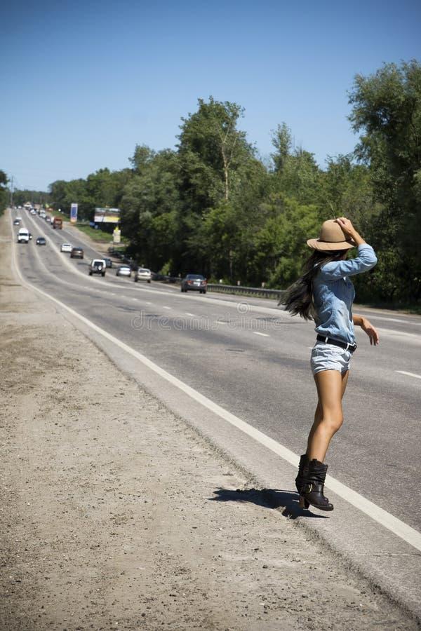 Mulher bonita nova que viaja ao longo de uma estrada foto de stock royalty free