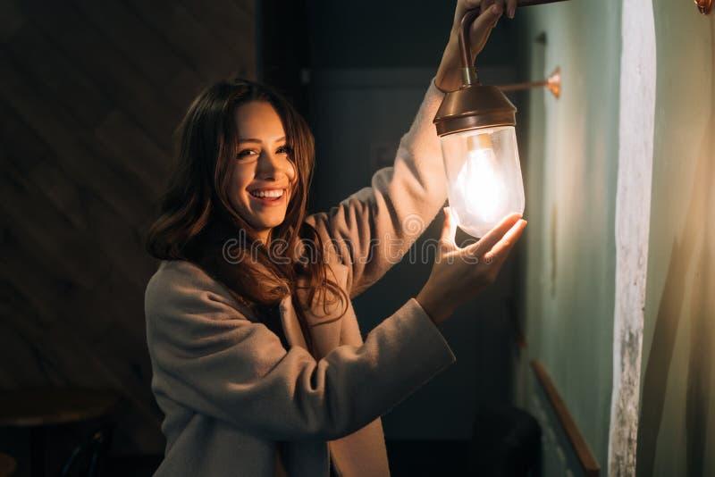 A mulher bonita nova realiza em sua mão uma lâmpada de parede pequena imagens de stock royalty free