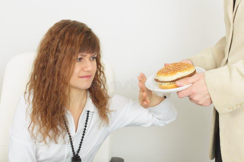 A mulher bonita nova recusa o alimento prejudicial fotos de stock