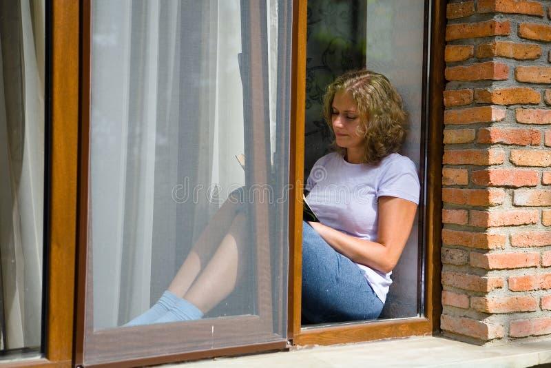 A mulher bonita nova senta-se na soleira e lê-se um livro fotografia de stock royalty free