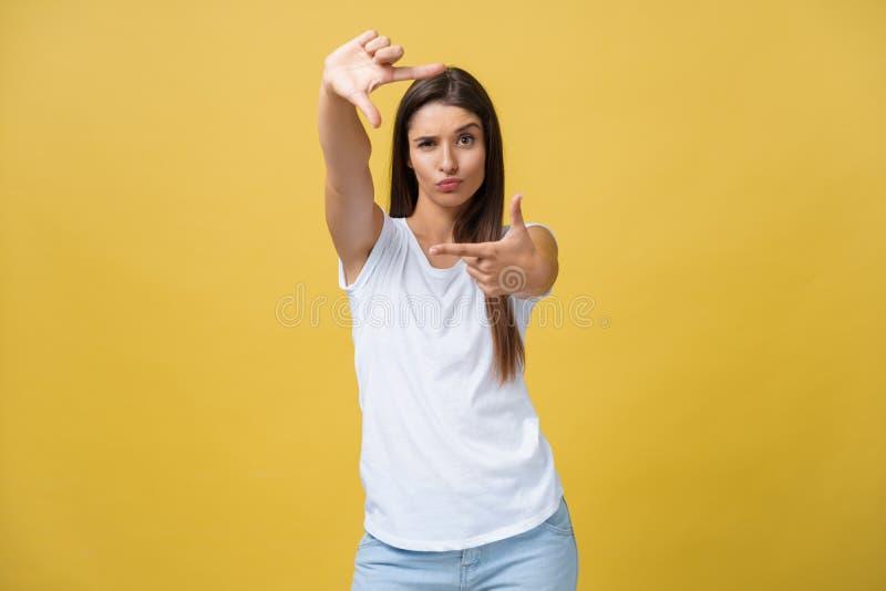 Mulher bonita nova sobre o fundo amarelo que sorri fazendo o quadro com mãos e dedos com cara feliz foto de stock
