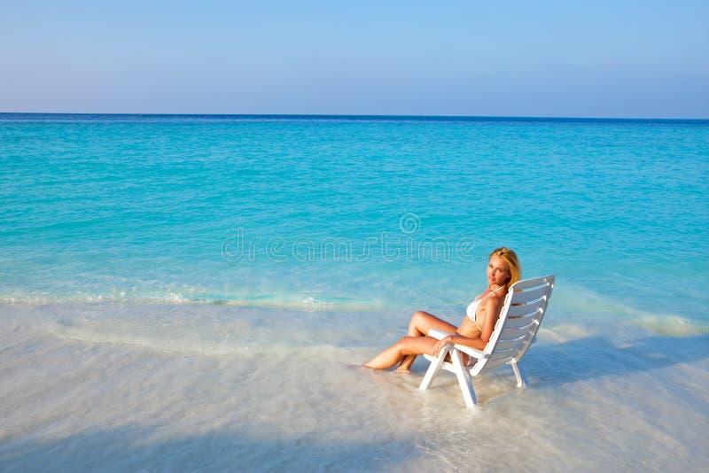 A mulher bonita nova tans na cadeira de praia foto de stock