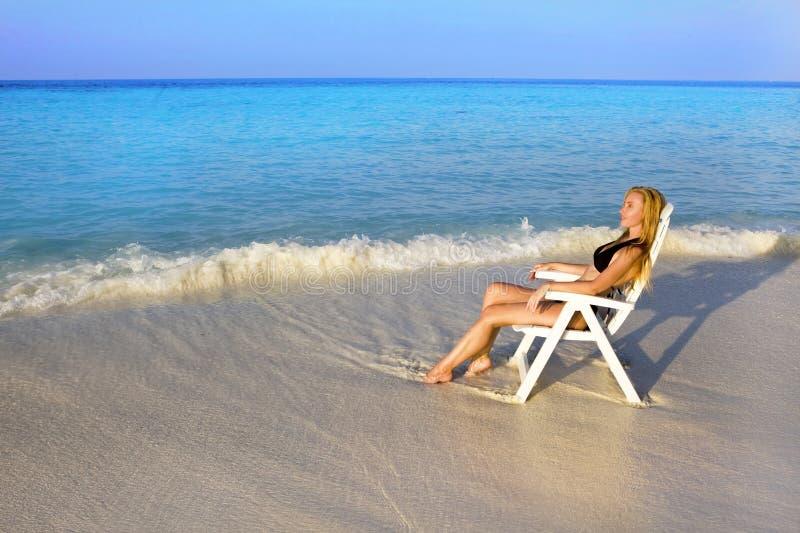 A mulher bonita nova tans na cadeira de praia no oceano foto de stock