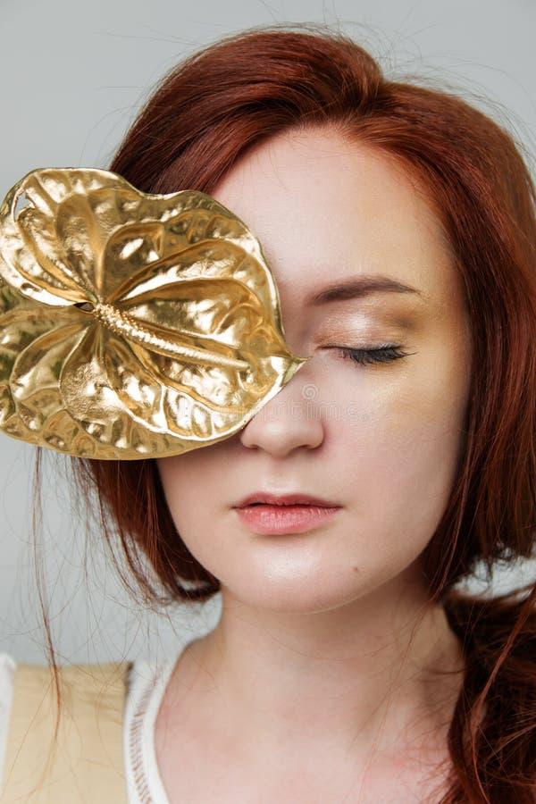A mulher bonita nova tem o cabelo que vermelho o ouro criativo compõe está levantando em um estúdio com flores fotografia de stock royalty free