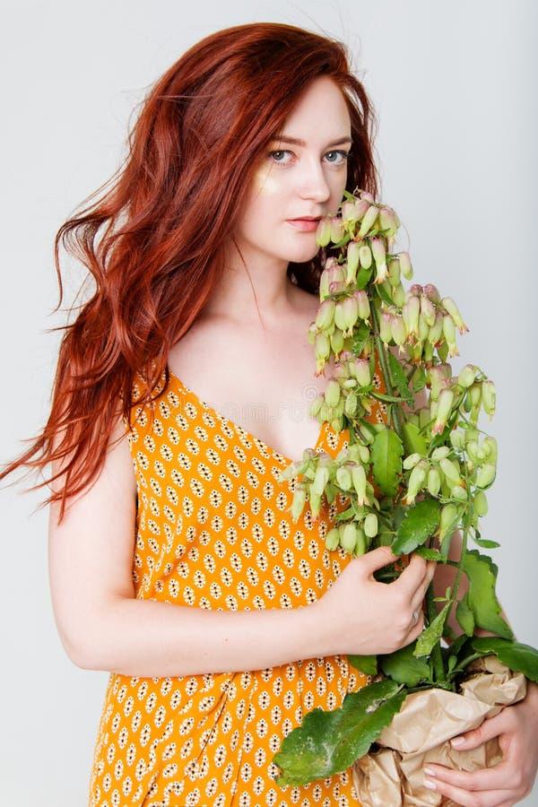 A mulher bonita nova tem o cabelo que vermelho o ouro criativo compõe está levantando em um estúdio com flores fotos de stock