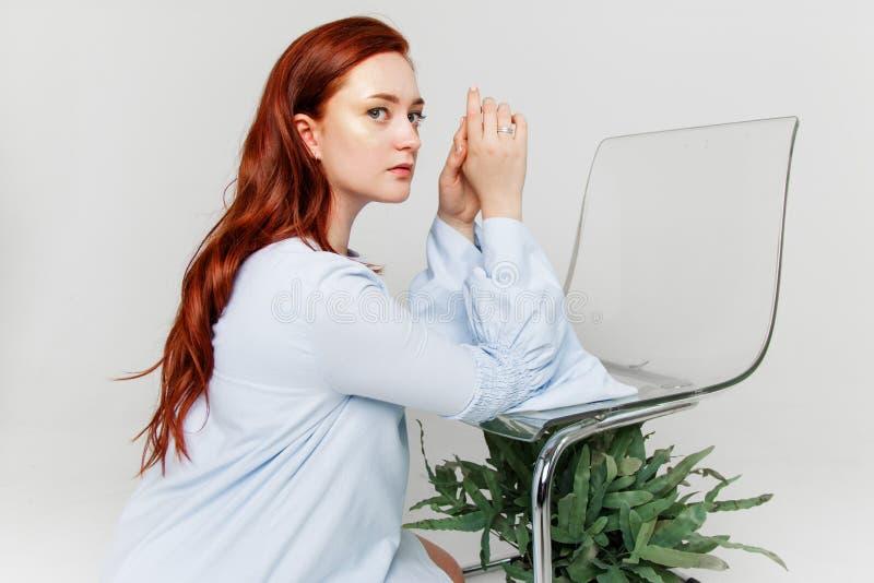 A mulher bonita nova tem o cabelo que vermelho o ouro criativo compõe está levantando em um estúdio com flores imagens de stock royalty free