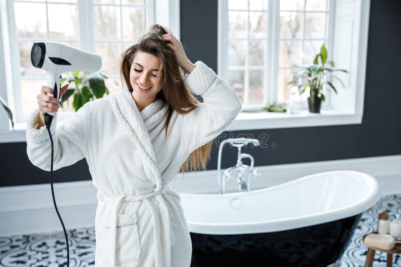 A mulher bonita nova vestida no vestido de pingamento branco conduz seu cabelo com um secador de cabelo em um banheiro bonito imagens de stock