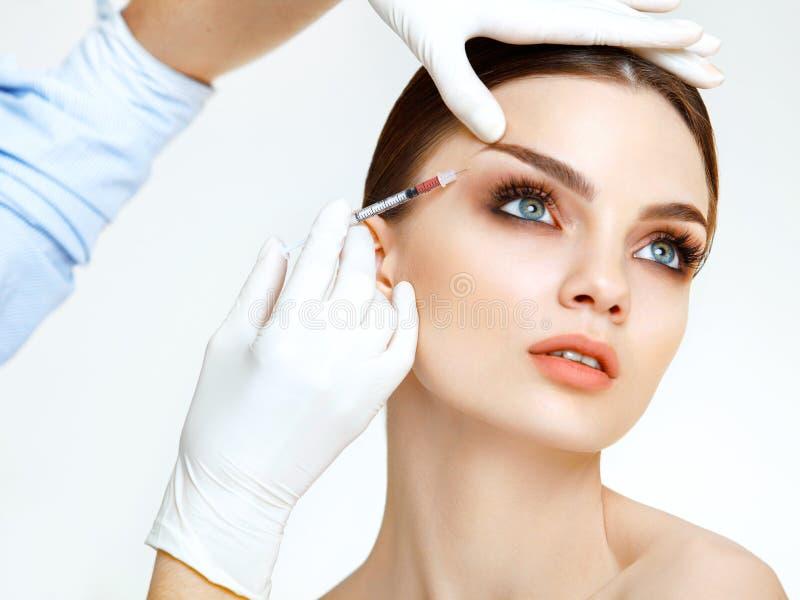 A mulher bonita obtém injeções. Cosmetologia. Cara da beleza imagens de stock
