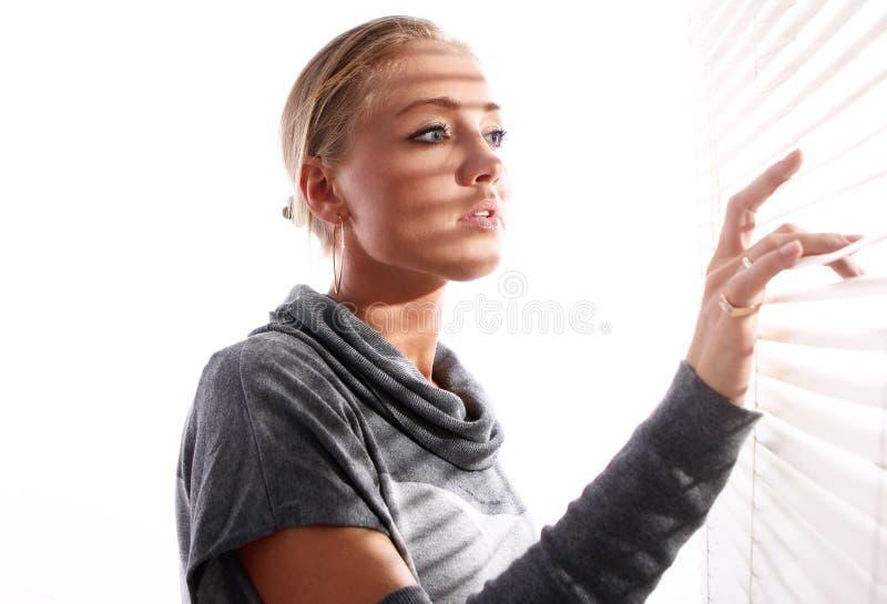 A mulher bonita olha através do jalousie fotografia de stock