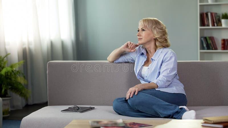 Mulher bonita pensativa que relaxa no sofá em casa, aposentadoria do tempo livre, lazer imagens de stock