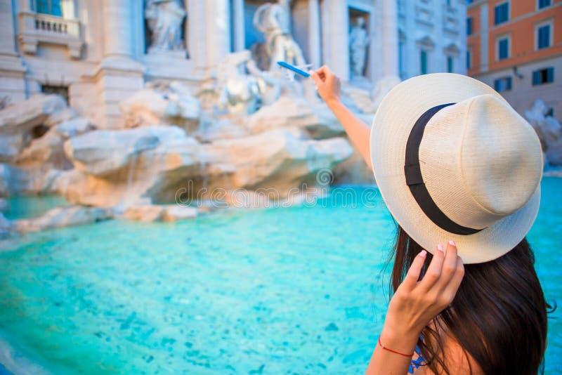 Mulher bonita perto da fonte do Trevi, Roma, Itália A menina feliz aprecia o feriado italiano das férias em Europa imagem de stock royalty free