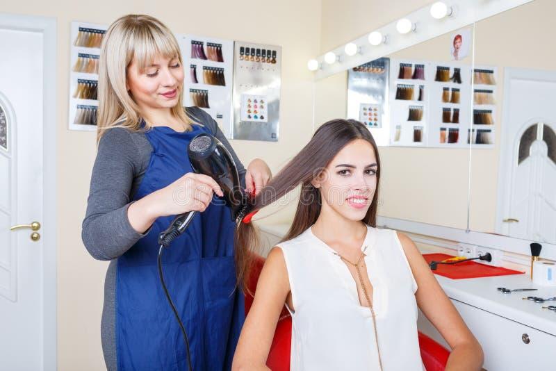 A mulher bonita positiva em um barbeiro que obtém lhe o cabelo tingiu-se em um fundo borrado Conceito do penteado fotos de stock royalty free