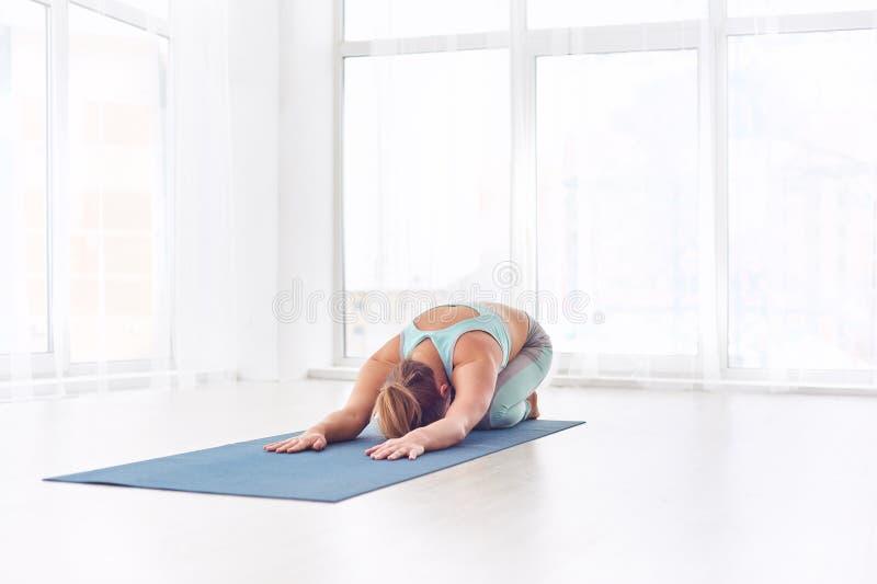A mulher bonita pratica o asana Balasana da ioga - pose do ` s da criança no estúdio da ioga imagem de stock