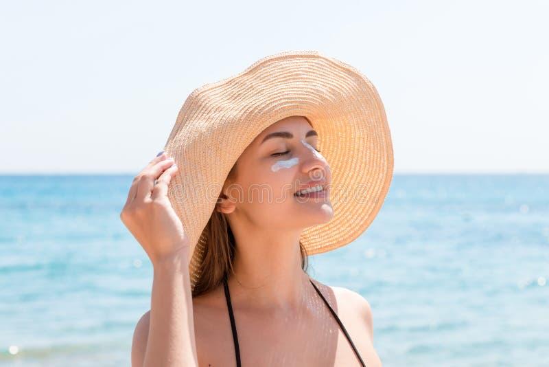 A mulher bonita protege sua pele na cara com sunblock na praia foto de stock
