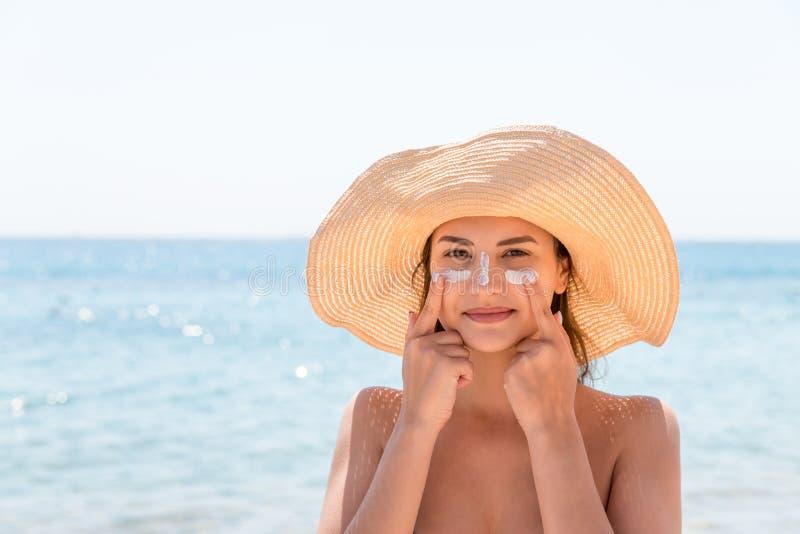 A mulher bonita protege sua pele na cara com sunblock na praia fotografia de stock