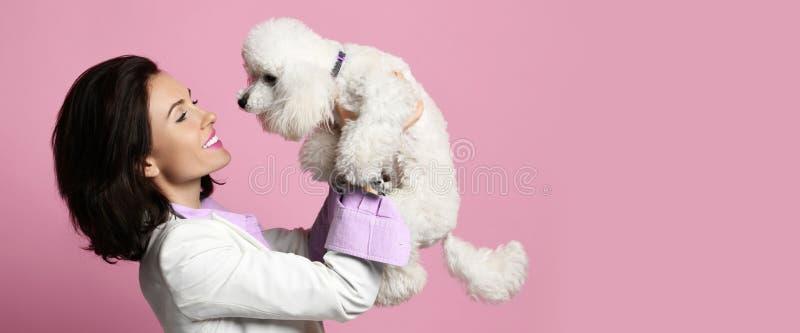 Mulher bonita que abraça seu cachorrinho branco bonito do cão de caniche no sorriso feliz cor-de-rosa fotografia de stock royalty free