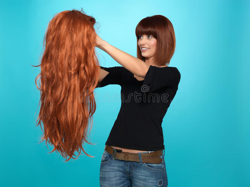 Mulher bonita que admira a peruca longa do cabelo fotografia de stock royalty free