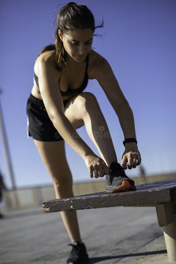 Mulher bonita que amarra sapatas em um banco de madeira na praia da frente marítima de Barcelona & no x28; ESPANHA fotografia de stock