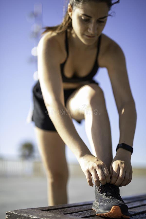 Mulher bonita que amarra sapatas em um banco de madeira na praia da frente marítima de Barcelona & no x28; ESPANHA imagens de stock royalty free