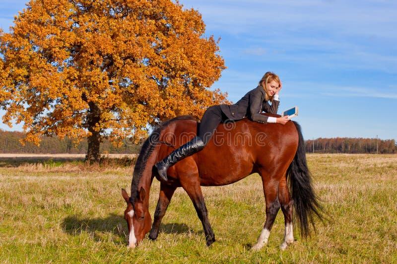 Mulher bonita que anda com cavalo fotografia de stock royalty free