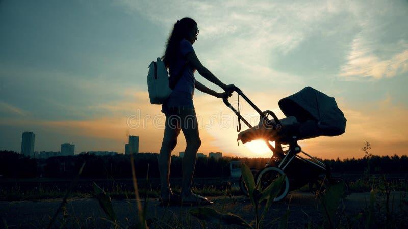 Mulher bonita que anda com um carrinho de criança no parque da cidade no por do sol foto de stock royalty free